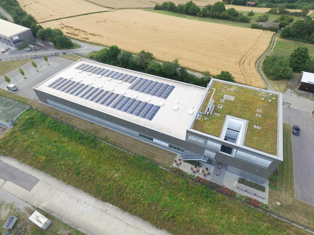 """Aerial View of the company building with solar panels and green roof"""